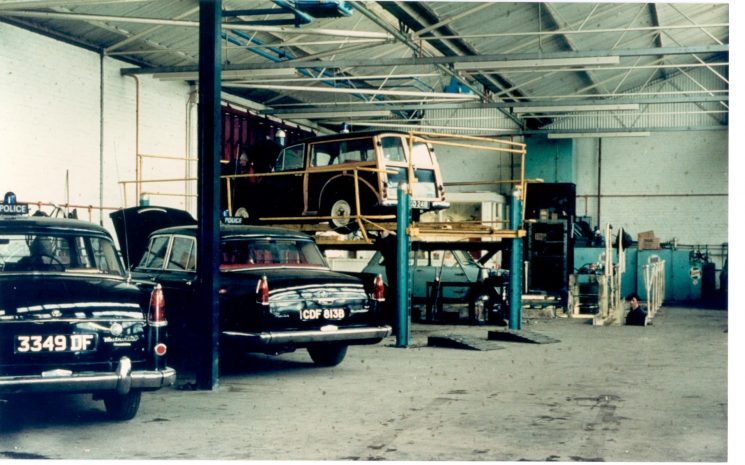 Police Vehicle Workshops at Cole Avenue Gloucester. Vehicles shown left to right two Austin Westminster Patrol cars, Morris Traveller (on ramp) and Austin Mini 1960. (Gloucestershire Police Archives URN 1167)