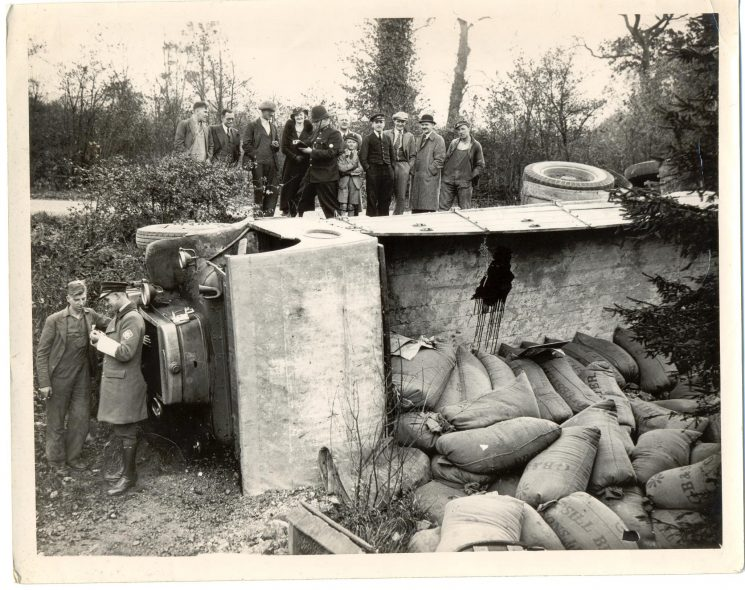 A crashed lorry, one uniformed Police constable and an Royal Automobile Club man along with a few members of the public. (Gloucestershire Police Archives URN 1381)