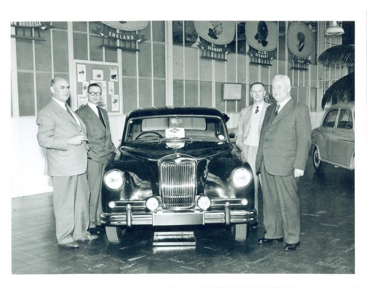 Taking delivery of new Riley Pathfinder  patrol car from show room at North Street Motors in Cheltenham Far left - Superintendent. H. J. Greenall ; far right - Superintendent C. P. Oakley. Others are North Street Motors staff members. (Gloucestershire Police Archives URN 1429)