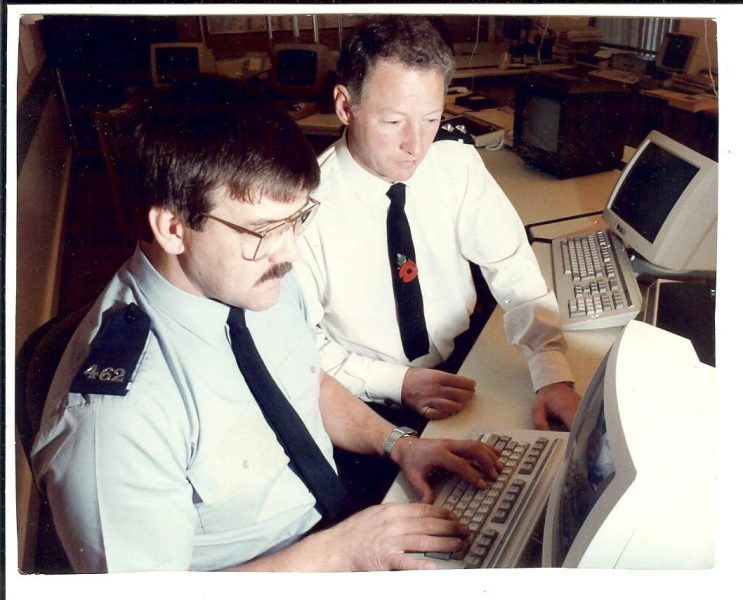 Inspector  Cyril Smith and Police Constable Colin Manton demonstrating new equipment in what had been the Force Information Room on it's change to a HQ & Northern Control Room following installation of new radio control, telephone & hilltop equipment together with Command & Control computers.The Information Room, Divisional & Sub-divisional control room were amalgamated into two Area Control Rooms based at Holland House (HQ) and Gloucester Bearland. This included changes to shift patterns, conditions of service for civilian operators and inclusion of inspector & sergeant stations on to a new digital Force Information Technology network. At the same time another project delivered the first Command and Control system. (Gloucestershire Police Archives URN 1505)