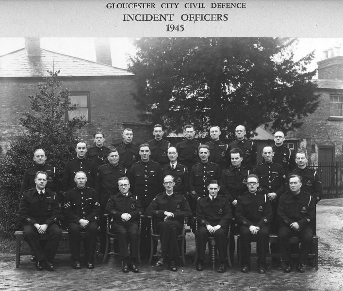 Gloucester City Civil Defence Incident Officers - mixture of police and civilians. Front row left to right: R.A. Sweet; Police Sergeant Harry Olpin; P.D. Clarke; Dr H.J. Larcombe; H.H. Jones; J.W. Seel; C.R. Gabb. Second row left to right: F.R. Ware; Police Constable F.R.W. Marsh; H .Wardle; Police Constable F. Grinnell; G. Dallard; Police Constable W.H. Tilling; V.E. Connor; Police Constable A. Smith; E.W. Walker. Third row Left to right: B.V. Charrison; J.H. Cooper; S.W. Harvey; A.E. Fey; Hager; R.S. Griffiths; J. Riley. (Gloucestershire Police Archive URN 1702)