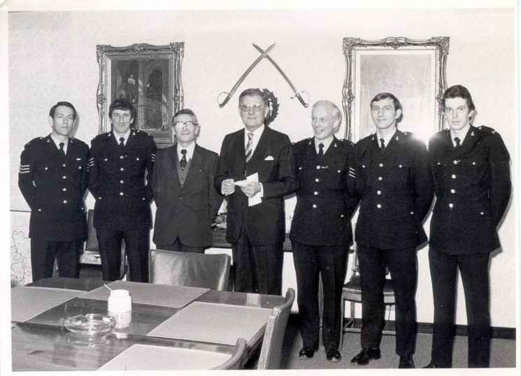 Presentation of cheque by officers who ran in Gloucester Marathon in aid of Multiple Sclerosis 1982. Left to right Police Sergeant Eddie Baud, Police Sergeant Phil Cluley, Unknown, Mr Charles Irving Member of Parliament, Police Sergeant  Mike Richards, Police Constable Dave Stacey,  Police Constable John Henry. (Gloucestershire Police Archives URN 354)