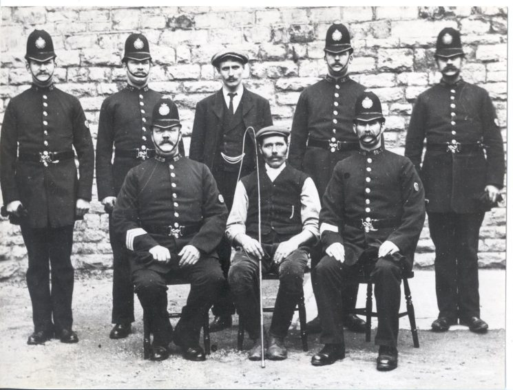 Staff at Stroud Police Station 1906. Named officers: left to right standing:  Police Constables Dance,  Loveday,  Wintle, unknown. Seated Police Sergeant Hale, Police Constable Simpson, Police Constable Deakins. (Gloucestershire Police Archives URN 48)