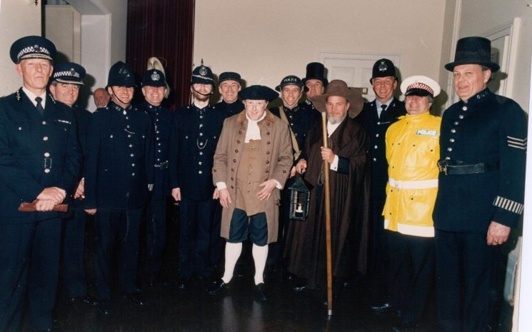 Members of the Police Choir dressed up for their 'party piece' a comedy routine to the tune of Jimmy Brown on the occasion of the 150th anniversary concert at the Town Hall Cheltenham 1989. (Gloucestershire Police Archives URN 522)
