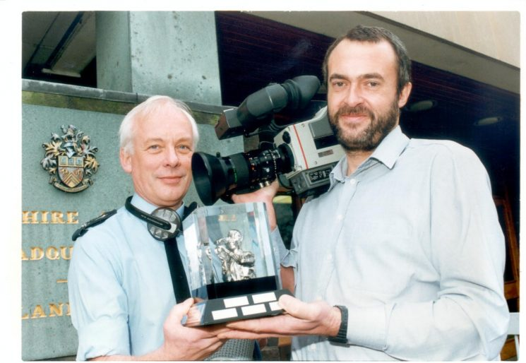 Police Video Awards 1990. Police Sergeant Mike Richards and Senior Technician Richard Haddon receiving the Award for the best police briefing video tape at a reception in London hosted by Nick Ross of Crime Watch. (Gloucestershire Police Archives URN 543)