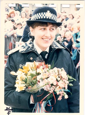 Woman Police Constable Robertshaw holding a bouquet of flowers at an unknown event. 1980s. Perhaps a royal visit? (Gloucestershire Police Archives URN 620)