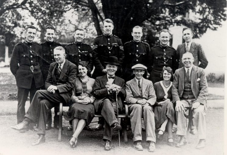 Headquarters staff 1932-33. Back row: Police Constable H. Boucher, Police Constable Robinson, Police Sergeant A. Newman, Police Sergeant  A.H. Carter (later Deputy Chief Constable,) Police Constable  Hamilton, Police Constable  Oakley, Detective Constable Walkley. Front row: Detective Sergeant A. Hancock, Hilda Spooner (Typist), Deputy Chief Constable Goulder, Chief Superintendent A. Sainsbury, Florence Ford (Typist,) Detective Inspector J. Green. (Gloucestershire Police Archive URN 84)