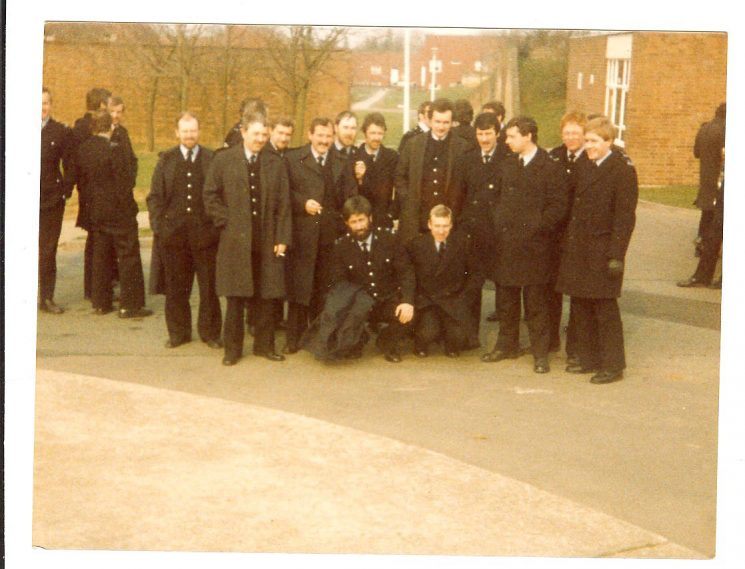 Group of officers at Gamecock Barracks  Warwickshire, during miners' strike. April 1984. Left to Right of the main group but some need filling in Keith Hawtin, Martin Cooke, Courtenay Humphries, Simon Moulding, Roger Vick, Dennis Massey, Glen McGlade, Geoff Clarke. Kneeling is Bob Easter and Eric 444 Moore. (Gloucestershire Police Archives URN 978)