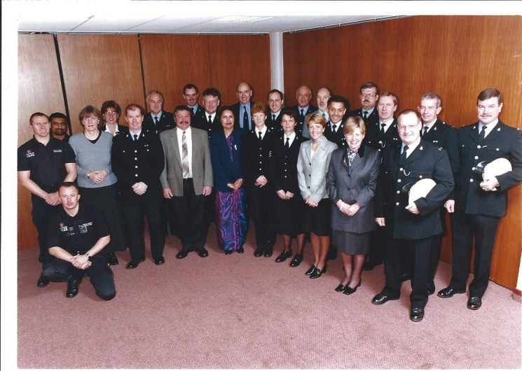 Training Department Staff, Wilton House, Cheltenham, thought to be 1999. Left to right: Police Constable Chris Perrett; Police Constable Paresh Bhadeshia;  Erica Bullock; Clare James; Police Constable  Alan Bartholomew; Police Constable  John Squires; Mick Blackford; Police Constable Mark Wood; Inspector Charlie Thomas; Baljeet Mann;  Richard Allen;  Police Constable Judith Davies; Police Sergeant Phil Offord; Police Sergeant  Lyn Vanstone; Police Constable  Steve Willis; Derek Arnold; Jan Patten; Police Constable  Wayne Wright; Anne Griffin; Police Constable Dave Webb;  Police Constable Chris Ellis; Police Constable Byron Chandler; Police Constable Keith Buggins; Police Constable Adrian Mansell; Shane Wood kneeling. (Gloucestershire Police Archives URN 1993)