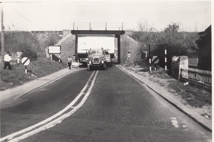 1966 a mobile classroom being moved through Andoversford on its way to Fishponds. The railings on the right of the photograph are outside the police station (Gloucestershire Police Archives URN 2095)