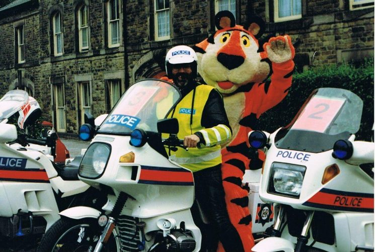 1991 Kelloggs Tour of Britain. Police Constable Martyn Hillier and Tony the Tiger in Buxton as part of the team escorting the cyclists around the country from Windsor to Leeds (Gloucestershire Police Archives URN 2394) | Photograph from Martyn Hillier