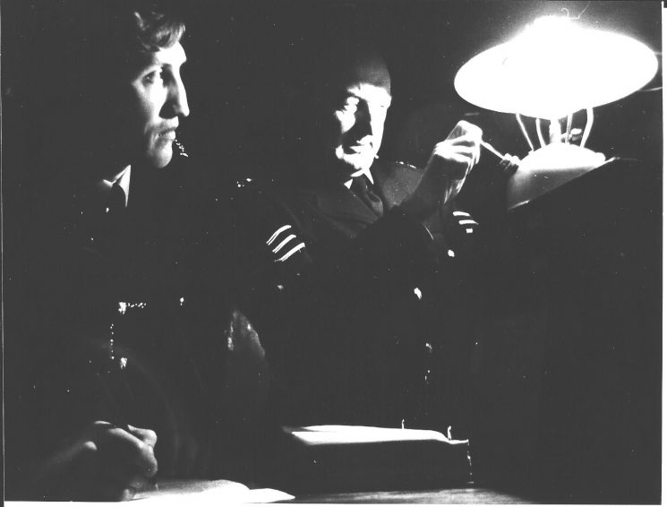Police Sergeant 553 Des Gay of Chipping Campden with Police Constable (later Inspector) Wayne Freeth-Selway writing reports by gas-lamp probably during the power-cuts of the 1970's. (Gloucestershire Police Archives URN 2062 )