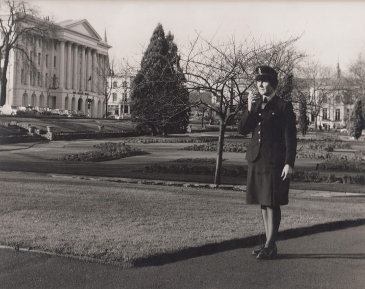 Woman Police Constable Monica Juggins using PYE pocket-phone UHF radio in Imperial Square, Cheltenham, circa 1970. (Gloucestershire Police Archives URN 2103)