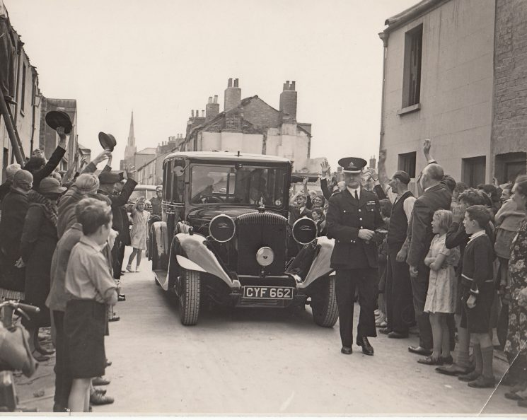 Visit by officials to bomb damaged street (Stoneville St) in Cheltenham. Superintendent Arthur W Hopkins walking in front of the car. (Gloucestershire Police Archives URN 2081)