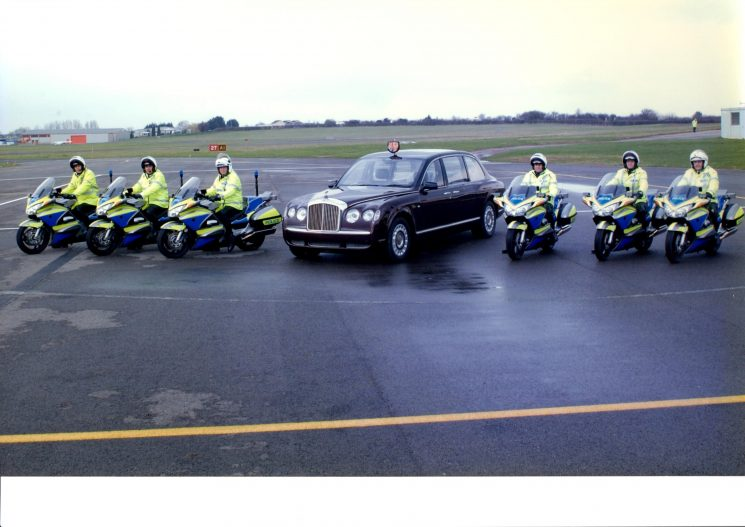 Royal car flanked by 6 Main Road Motor cyclists at Staverton airport. From left to right: Mark Dimond, Ian Kay, Simon Meredith,Mike Fitter, Gordon Parr, Ian Lloyd.(Gloucestershire Police Archives URN 2236)