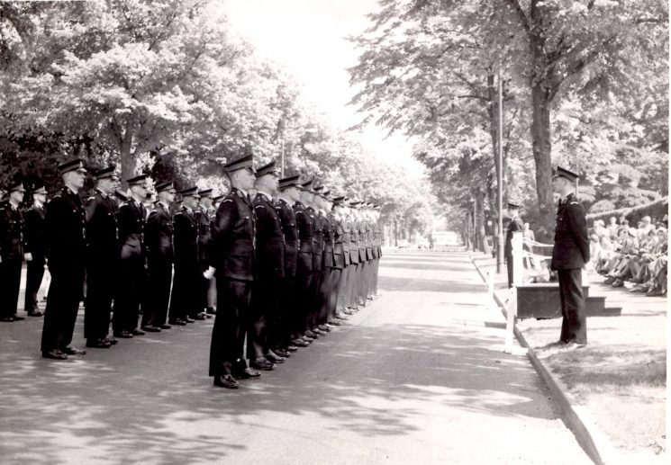 Police Cadet inspection in Lansdown Road Cheltenham. The cones closing the road towards Westal Green are just visible  past the cadets. In front of the parade Clive Fluck and Vince Castle. Back row first cadet Robin Haines. Middle row left to right: Derek Fry; Bob Bridge: unknown; Dave Thompson; Brian Bailey. Front row left to right:  Pete Kilbey; Tony Blyth; Chris Phillips; Adrian Wallace; Ricky Hall; Tom Taylor. (Gloucestershire Police Archives URN 2124) | Photograph from Pete Kilbey