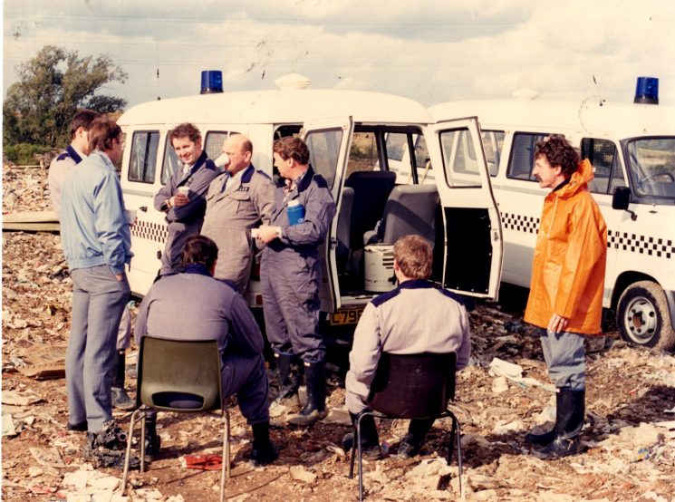 Searching the tip for evidence after a murder. Standing left to right; Kim Pembridge; Mike Foley;  Dave Stevens, Pete Kilbey; Brian Frusher;Paul House. Seated: Bob Creed and Keith Fagin. (Gloucestershire Police Archives URN 2134) | Photograph from Pete Kilbey