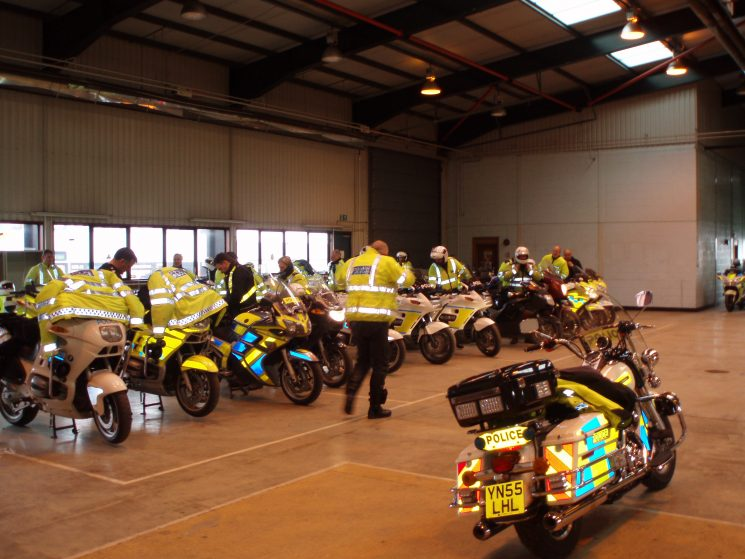 2005 was the first year that Gloucestershire Constabulary hosted the National BikeSafe  show at Cheltenham Racecourse. Police motorcyclists came from all over the United Kingdom. Here a number of officers are parking up their machines for the night in the old workshops at Bamfurlong. (Gloucestershire Police Archives URN 2162) | Photograph from Martyn Hillier
