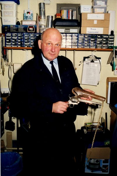 Pete Kilbey  with Billy the Kid's pistol. This was surrendered during the firearms amnesty after the Dunblane Massacre in 1996. (Gloucestershire Police Archives URN 2139) | Photograph from Pete Kilbey