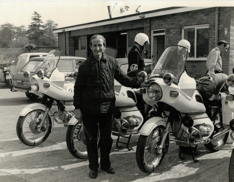 The day we put the 4 new (first) BMWs on the road, in 1976. Mr Bill Bacon, of the HOWMU ! It was always called Radio Workshops, but any official correspondence was always  to the Home Office Wireless Maintenance Unit. Bill fitted radios to the cars and bikes. From left Bill Bacon, Police Constables Andy Hampton, Martyn Hillier and Traffic Sergeant Ken Hughes. (Gloucestershire Police Archives URN 2210) | Photograph from Martyn Hillier