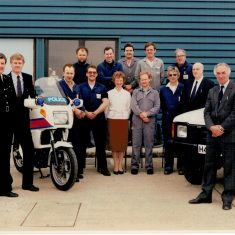 Early 1990s - new workshops open at Bamfurlong Left to right: Superintendent Joe Skipsey,Mike Barwick (Fleet Manager) Clive Morefield, Mike Rowles, Paul Elston, Peter Davies, Mrs Pam Emmet,  Rob Stanley,  John Arscott, Rod Stone, Dennis Woodward, Pat Harris, Brian Curtis and Len Whitty. (Gloucestershire Police Archives URN 2271) | Photograph from Martyn Hillier