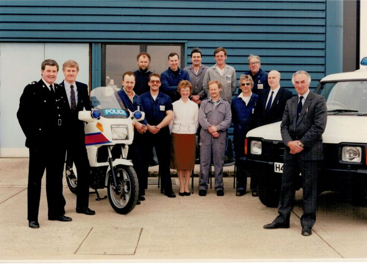 Early 1990s - new workshops open at Bamfurlong Left to right: Superintendent Joe Skipsey,Mike Barwick (Fleet Manager) Clive Morefield, Mike Rowles, Paul Elston, Peter Davies, Mrs Pam Emmet,  Rob Stanley,  John Arscott, Rod Stone, Dennis Woodward, Pat Harris, Brian Curtis and Len Whitty. | Photograph from Martyn Hillier