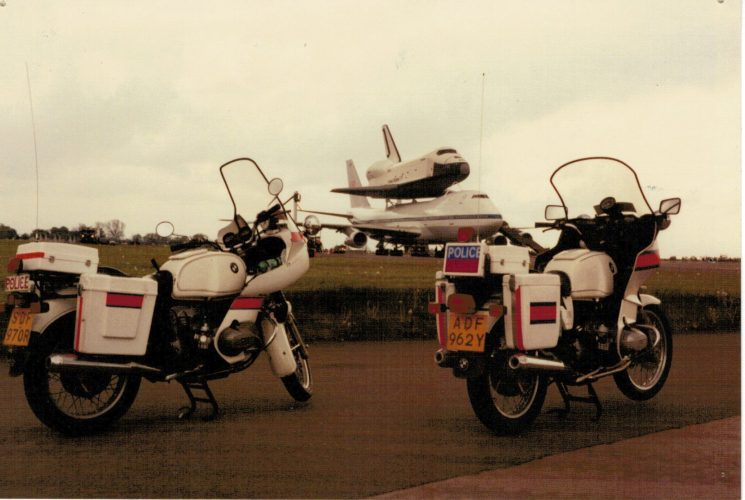 The space shuttle landed at Royal Air Force Fairford as part of a European tour, taking in various events, including the Paris air-show. Obviously the motorbikes are much more interesting and so are the focus of the photograph. (Gloucestershire Police Archives URN 2268) | Photograph from Martyn Hillier