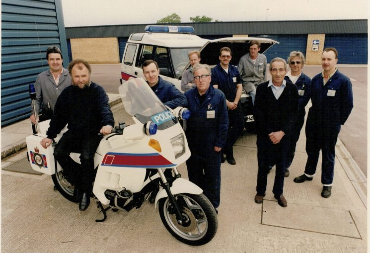 Workshop staff, late 1980s. Left  to right Rob Stanley, Mike Rowles, Peter Davies, John Arscott (face half hidden) Pat Harris, Paul Elston, Rod Stone, Derek Teague, Dennis Woodward and Clive Morefield. (Gloucestershire Police Archives URN 2263) | Photograph from Martyn Hillier