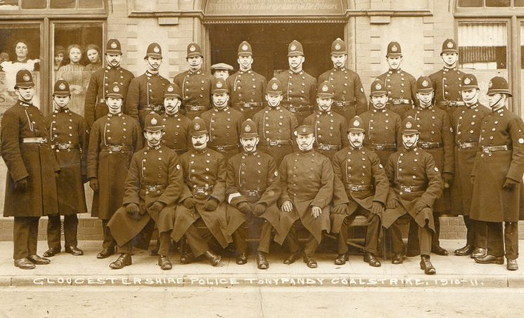Gloucestershire officers at Tonypandy miners strike 1910-11. Back Row from left to right: Police Constables William Clarke; Charles Coldicott; William Fry; Arthur Ewans; Francis  Wood; Henry Boulton; Charles Betteridge; Harold Thompson. Middle row left to right: Police Constables William Hands; Ralph Crook; Alfred Tennant; Charles Bull; James Case; George Wickham; William Merrett, Henry Mainstone; William Bayliss; Percy Bowrey; William Pinnions. Seated left to right: Police Constables William Strawford; Henry Strickley; Police Sergeant Robinson, Inspector Dennis; Police Constables Hubert Stephens, Harold Illes. (Gloucestershire Police Archives URN 1385)