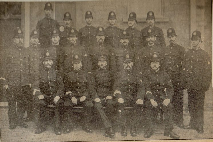Back row from left to right: Police Constable Hiron (Kemble), Police Constable Greengrass (Tetbury), Police Constable Poulton (South Cerney), Police Constable Wood (Fairford), Police Constable Antell (Cirencester) Police Constable Hands (North Cerney) . Middle Row left to right: Police Constable Cleavely (South Cerney); Police Constable Core (Sapperton); Police Constable Baskett (Tetbury); Police Constable Bullock (Cirencester); Police Constables Aston and Durant (Lechlade); Police Constables Ball, Hamblin, Corbett (Cirencester). Front row left to right: Police Sergeant Smith (Tetbury); Police Sergeant Neville and Superintendent Webb (Cirencester); Police Sergeant Jenkins (Fairford); Police Constable Long (Bibury. (Gloucestershire Police Archives URN 2309)