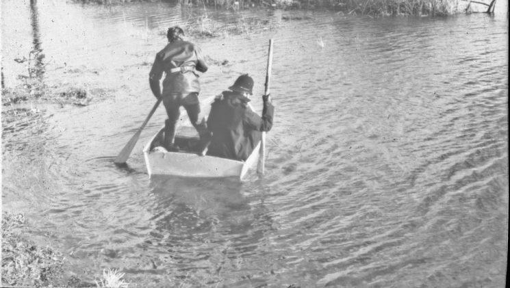 Two police officers in a boat looking for missing children in Tewkesbury.(Gloucestershire Police Archives URN 2487) | Photograph from an old negative