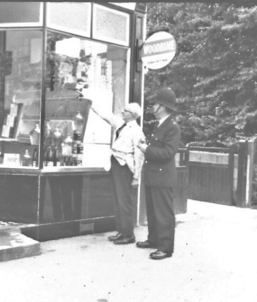 Police officer and a shopkeeper looking at a broken shop window. (Gloucestershire Police Archives URN 2476) | Photograph from an old negative