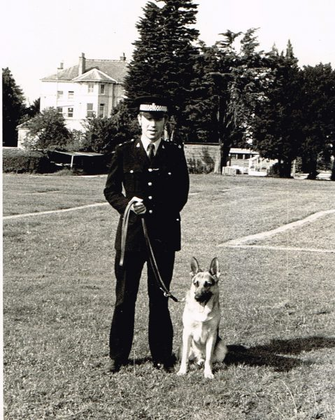 John Taylor  police dog handler from 1980 – 86 with Police Dog Marcus trained in county by Police Constable Ben Smith and Police Constable Dave Carter. Taken at  Bishops Cleeve playing fields 1980. (Gloucestershire Police Archives URN 2362) | Photograph from John Taylor