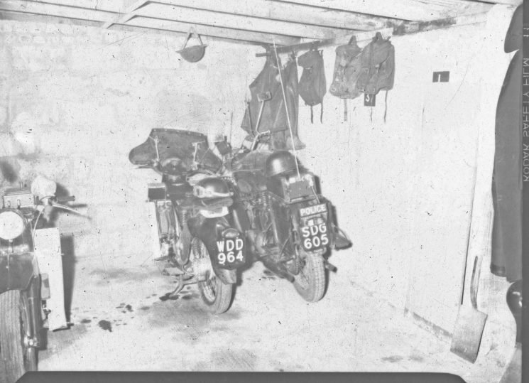 Police motorcycle and equipment in garage. (Gloucestershire Police Archives URN 2485) | Photograph from an old negative