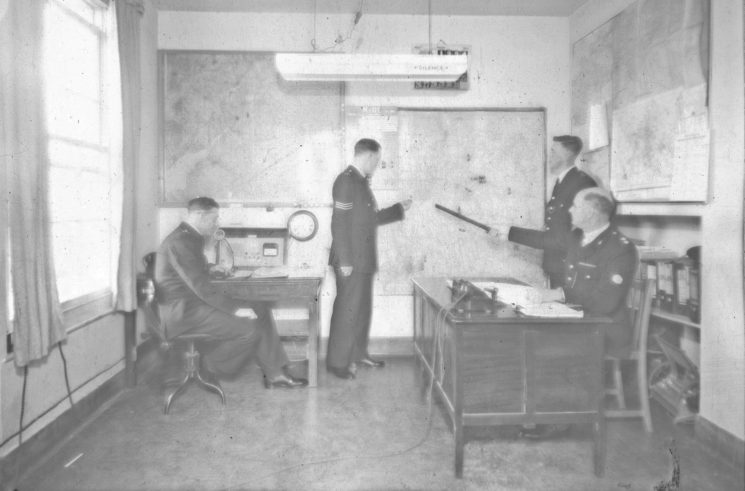 An Inspector, Sergeant and Police Constable and another officer in Information  room. (Gloucestershire Police Archives URN 2469)   Photograph from an old negative