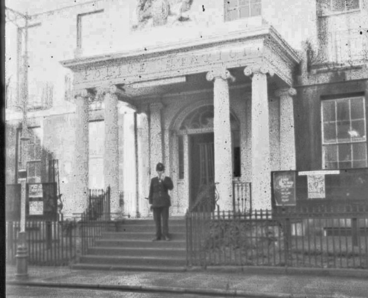 Officer standing on the steps of  Cheltenham Police Station, Crescent Place, by the uniform is probably mid 1950s. (Gloucestershire Police Archives URN 2463) | Photograph from an old negative