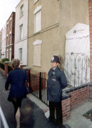 A policeman stands guard at the front of 25 Cromwell Street as a woman walks past Oct.19 1995. Jurors in the Rosemary West trial will today visit the home of the West's where she is accused of murdering 10 women.(Gloucestershire Police Archives URN 2618)