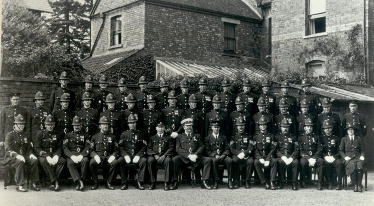 F Division 1932 at Lydney Police Station Back Row: Police Constables Bailey Crowther; AW Taylor; Lippett; Pagett; Cole; Green; Boughton; Baldwin; Phelps; Barnes; Jefferies; Hale. Middle Row: Police Constables Pole; Gay; Batchelor; Buck; Francis; Tuttiett; Minett; Beddis; Williams ;Day; Rogers; Cox; James; Randell; Fardon; Smith. Front Row: Police Constables Ireland; Weekes; Police Sergeants Coldicutt; Bull; Freeman; Inspector Green; Superintendent Shelswell; Inspector Large; Police Sergeants Hobday; Coates; Ferryman; Police Constables Taylor; Morris; Woman Police Constable Cameron. (Gloucestershire Police Archives URN 76)