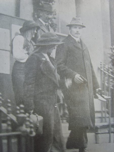 Detective Constable  379 Ernest Towell (Left) and Inspector John Whyton (Right) with two arson suspects in Cheltenham 1912 . On Sunday 21st December 1913 about 5 o'clock, a fire was observed to break out at Alstone Lawn , an empty mansion standing in the Gloucester Road Cheltenham surrounded by some acres of its own grounds, the fire brigade was promptly called and the place was almost miraculously saved, the firw having well got hold. Two unknown suffragettes were arrested the same morning and were remanded at the police court on Monday. Their boots and stockings which were soaked in paraffin were taken from them and they absolutely refused to put others on. They were taken to Worcester Gaol by Inspector Whyton and detective Towell, the former is carrying the shoes and stockings. They refused to put up their hair and went barefoot to Worcester. (Gloucestershire Police Archives URN 3465 )