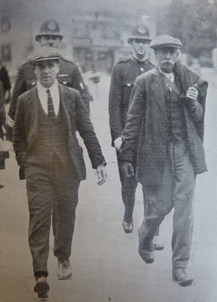 Two prisoners handcuffed together committed for trial at Gloucester Quarter Sessions being taken to the Great Western Railway Station Cheltenham on the way to Gloucester prison on Thursday September 30 1926. The prisoner on the left is Richard Claremont (19). He was sentenced to 5 years penal servitude for being caught with house breaking instruments and an automatic pistol and a magazine of cartridges. He was convicted of eight charges of house breaking when he was only thirteen years old. The prisoner on the right is Peter Dunne (56). He was sentenced to 12 months imprisonment with hard labour for the theft of a silver cigarette lighter worth £1 along with 2 shillings in money belonging to Mr. Scott Cooper - Jeweller of the Promenade. (Gloucestershire Police Archives URN 3601)