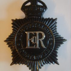 Black helmet plate from reign of Elizabeth II. This dates to  1952-53 as it  has the kings crown. (Gloucestershire Police Archives URN 6111 )