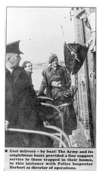 Inspector E. J. Herbert in boat delivering coal to stranded house during floods in Tewkesbury in 1947. (Gloucestershire Police Archives URN 572)