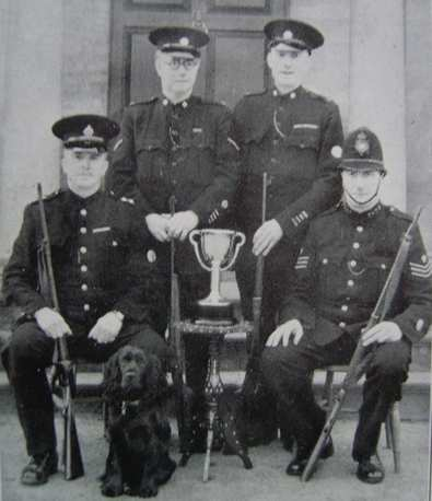 The D Division miniature rifle team, winners of the 1943 Lord Lieut's Musketry Challenge Cup. An annual competion held by Divisional teams, made up from Regulars and Specials. This team of Stroud and Dursley men scored 190 points out of a possible 200 (Gloucestershire Police Archives URN 6953)