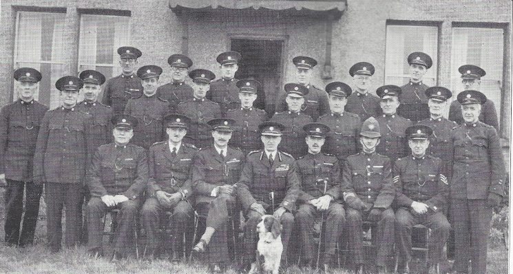 Thornbury Division Coalpit Heath Section. Back Row: Special Constables Mann, Rodman, Hulands, Vizard, Coombes, Elliott, Roberts. Middle Row: Special Constables Dando W, Dando G, Taylor, Tovey, Bennett, Hubble, Knight, Payne, Russell R, Berrett, Cole. Seated: Head Special Constable Russell M, Special Superintendent Nelson Rooke, Commandant Sleeman, Special Inspector Walker, Police Constable Prior, Police Sergeant Langley. (Gloucestershire Police Archives URN 6963)
