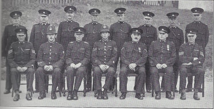 Thornbury Division North Nibley Section Back Row: Special Constables Parker, Purnell, Niblett, Mason, Browning, Evans, Meek, Sharp. Seated: Special Sergeant Keynton, Police Constable Midwinter, Special Inspector Brewer, Police Sergeant Auger, Head Special Constable Elliott, Special Constable Talboys,  Special Sergeant Jotcham.(Gloucestershire Police Archives URN 6969)