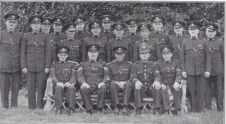 Thornbury Division Wickwar Subsection. Standing: Special ConstablesWithers, Day, Bridgeman A.J, Roberts, Fowler, Jones, Bridgman D, Pritchard, Marsh, Hall, Winbow, Nelmes, Wonnacott, Moore, Trembling. Seated: Head Special Constable Musty, Special Sergeant Leakey, Special Inspector Codrington, Police Constable Gardner, Head Special Constable Tovey (Gloucestershire Police Archives URN 6975)