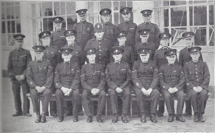 Cirencester Division Andoversford Subdivision. Back Row: Special Constables Winter, Packer, Cross, Daubeny, Ayres. Middle Row: Special Constables Smith, Fox, Mace, Police Constable Taylor, Special Constables Hicks, Kilbey, Bloxsome, Blacklock. Seated: Head Special Constables, Hiatt, May, Keene, Special Sergeant Abell. Head Special Constables Pudell, Hughes Police War Reserve Ralph. (Gloucestershire Police Archives URN 6979)