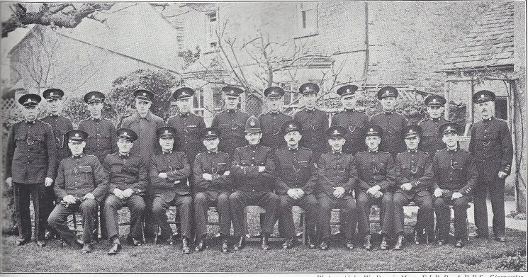 Cirencester Division Bibury Subsection Back Row: Special Constables Stallard, Smith, Bartlett A, Houlton, Jenkins, Jones, Norris, Brownett, Tyler, Clarke, Giles, Gwinnett. Seated: Special Constables Greenslade, Clements, Mills, Head Special Constable Robins, Police Constable Taylor, Special Sergeant Andrews, Head Special Constable Bartlett, Special Constables Lockey, Lucker, Edwards. (Gloucestershire Police Archives URN 6981)
