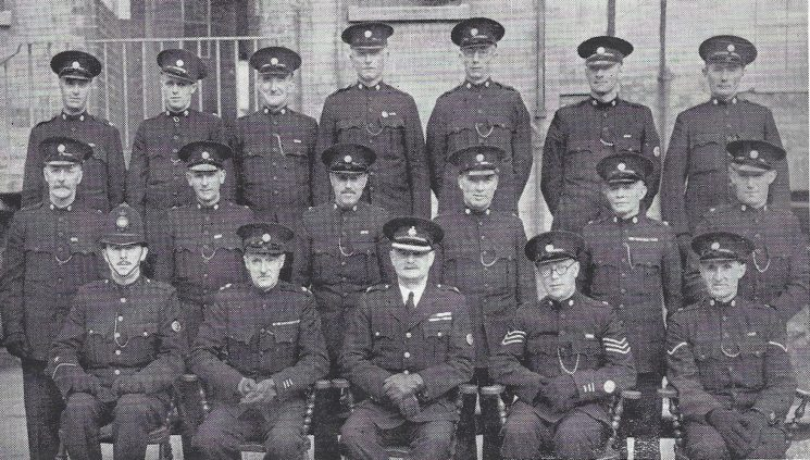Cheltenham Rural Division Coombe Hill Section. Back row: Special Constables Evans, Surman, Robinson, Smart, Sandells, Poulton, Theyer. Middle row: Special Constables Minchin, Parker, Andrews, Mansell, Carter, Cleverley. Seated: Police Constable Groves, Special Superintendent d'Arcy Fisher, Superintendent Hopkins, Special Sergeant Bennett, Head Special Constable Vedmore.(Gloucestershire Police Archives URN 7007)