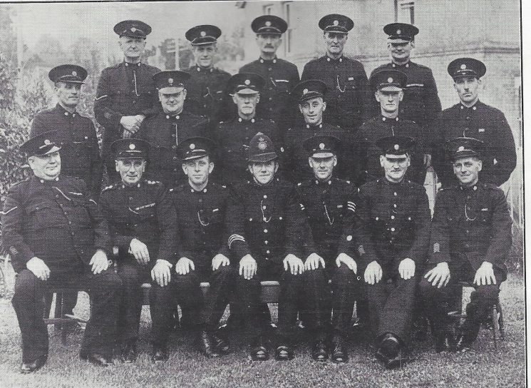 Gloucester Rural  Division Dymock Section. Back row: Head Specials Gibson, Smith, Special Constables Williams, Hyett R, Hyett G. Middle row: Head Special Constable Carless, Special Constables Gibson, Maile, Preece, Sayer, Burlow. Seated: Head Special Bayliss, Special Inspector Mann, Special Sergeant Chew, Police Constable Widdows, Special Sergeant Hobbs, Police War Reserve Hegarty, Special Constable Barnfield (Gloucestershire Police Archives URN 7010)